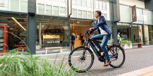 Man fiets op zijn elektrische fiets door een winkelstraat.