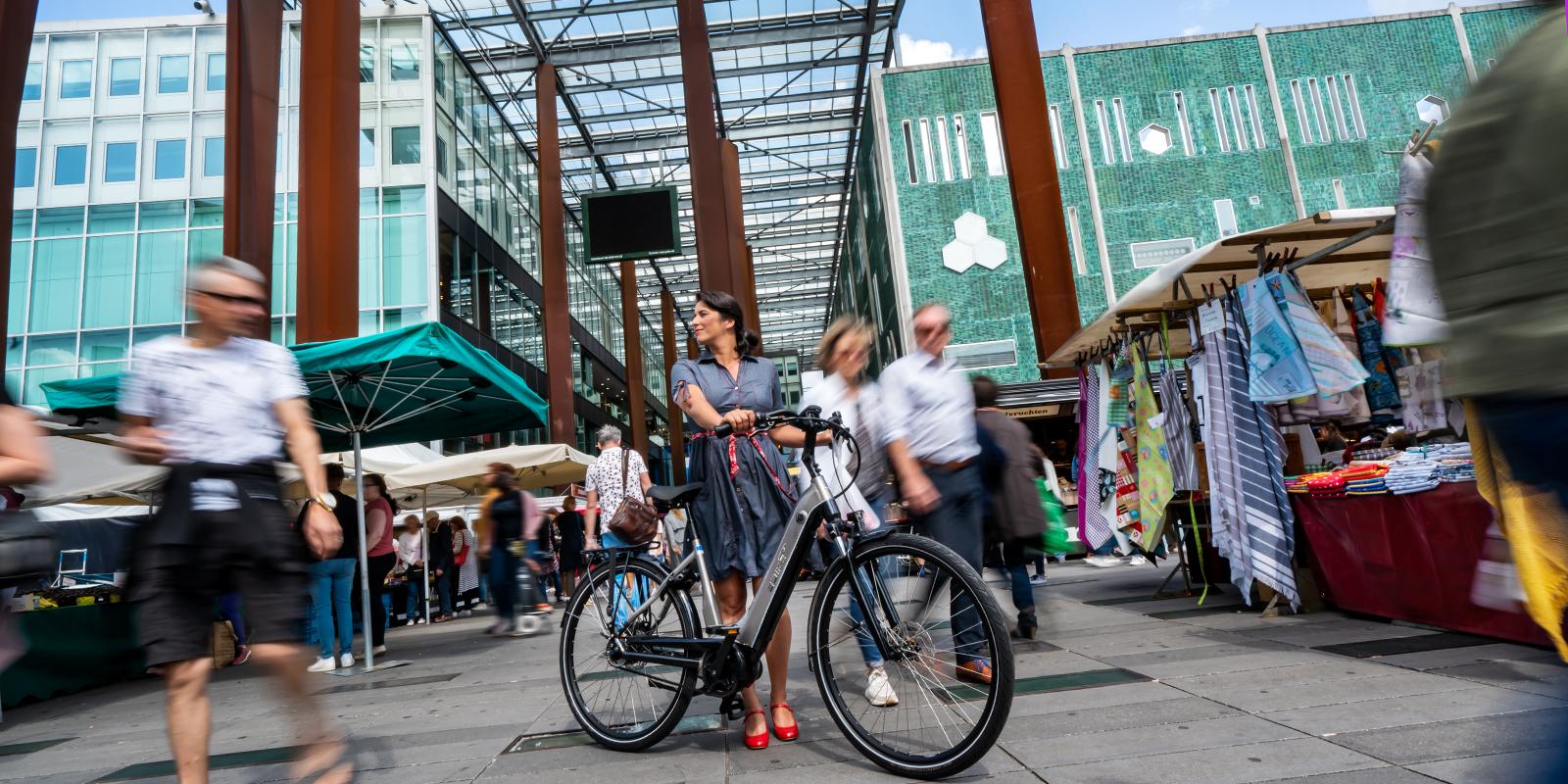 Mevrouw met E-bike in drukke winkelstraat.