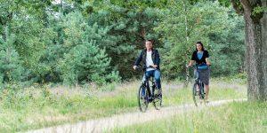 Meneer en mevrouw fietsen door het bos.