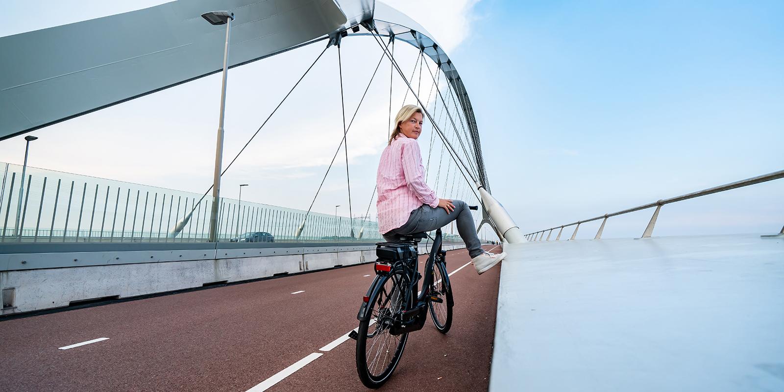 Mevrouw fiets op Ebike das original op het fietspad